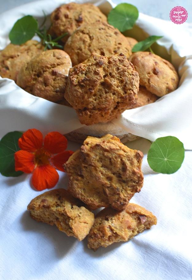 Kürbis-Speckweckerl im Brotkörbchen, davor angebrochene Weckerl und eine orangefarbene Kapuzinerkresseblüte