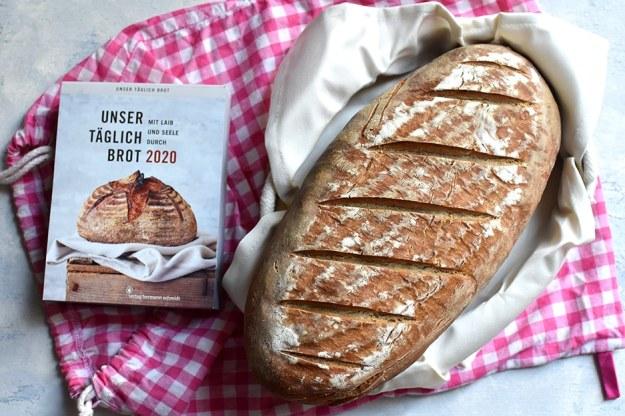 """Brotkörbchen mit einem Bauernbrotstrietzel, auf einem rosa-weiß karierten Brotsack, daneben der Tagesabreisskalender """"Unser täglich Brot. Mit Laib und Seele durch 2020"""""""