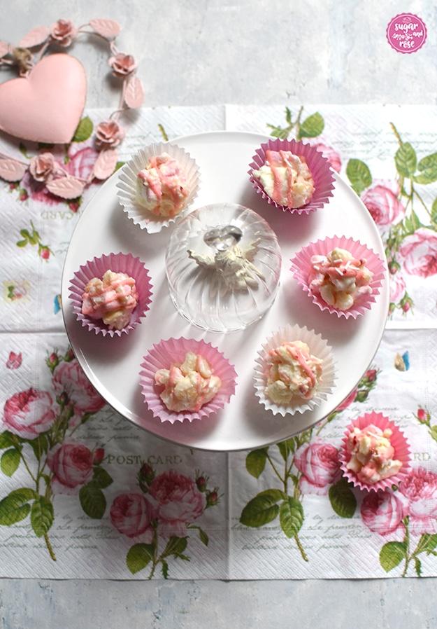 6 Stück Rocky Road Konfekt in rosa und weißen Pralinenförmchen auf einer weißen Keramikplatte, in der Mitte eine kleine weißer Engelfigur unter einem Miniglassturz