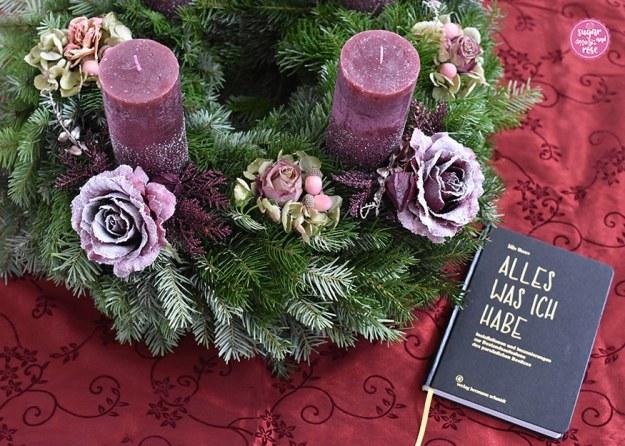 """Adventskranz auf weinrotem Damasttischtuch, davor ein schwarzes Buch mit Goldlettern """"Alles was ich habe"""""""