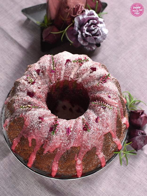 Punschgugelhupf mit rosa Zuckerguss auf Leinenserviette, dahinter eine rosegoldene Kerze auf einem Sternenteller, dekoriert mit einer auberginefarbenen Kunstrose mit Schneestaub