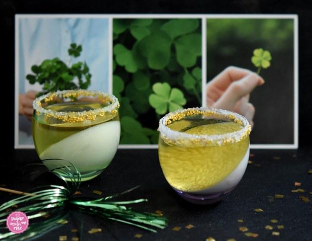 Zwei bauchige kleine Cocktailgläser mit Sektjelly, davor Goldflitter, dahinter eine Karte mit Glücksklee