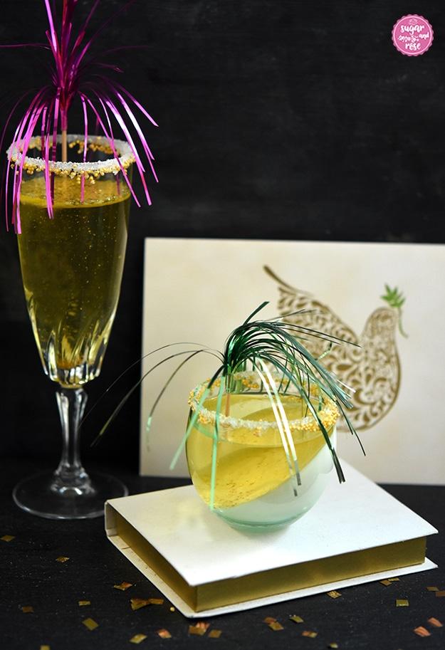 Ein hohes Sektglas mit Sektjelly und pink Deko, daneben auf einem weißen Buch stehend ein kleines bauchiges Glas mit Sektjelly und grüner Deko, dahinter eine Karte mit Friedenstaube als Motiv