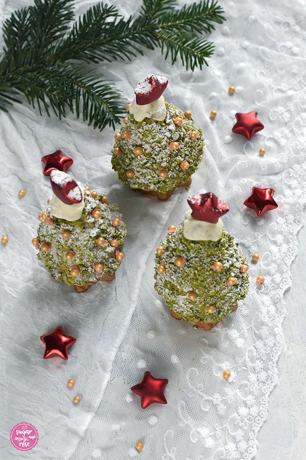 Drei Weihnachstbäume zum Vernaschen auf einem weißen Spitzendeckchen, an der Baumspitze rote Dekosterne, vorne kleine rote Dekosterne und goldene Zuckerperlen