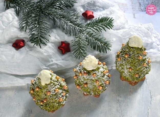 Drei Weihnachtsbäume zum Vernaschen mit Goldzuckerperlendeko in Reih und Glied vor einem weißen Spitzentuch und einem beschneiten Tannenzweig, dazwischen drei mattrote Dekosterne
