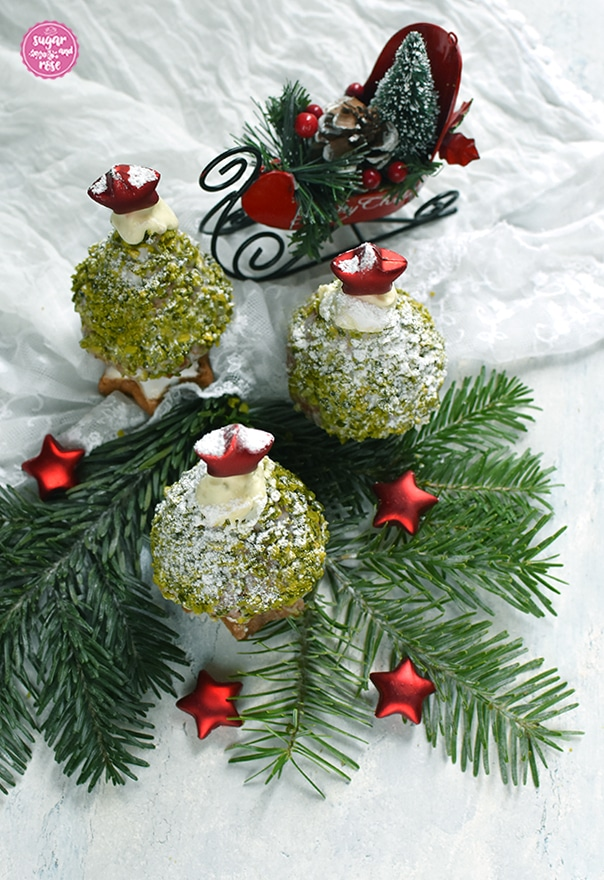 Drei Weihnachstbäume zum Vernaschen auf einem Tannenzweig, dahinter ein roter Dekoweihnachtsschlitten, vorne kleine rote Dekosterne