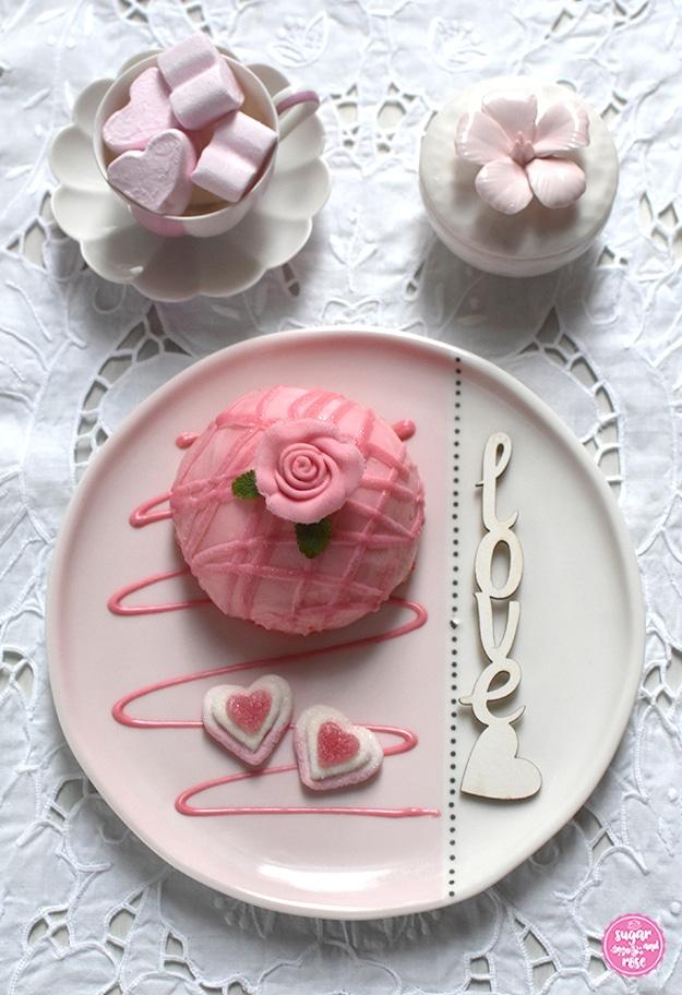 Ein Himbeer-Joghurt-Törtchen mit Dekorose auf rosa-weißem Keramikteller, dekoriert mit einem Love-Schriftzug, dahinter eine Augarten-Melone-Mokkatasse mit rosa Marshmallowherzen