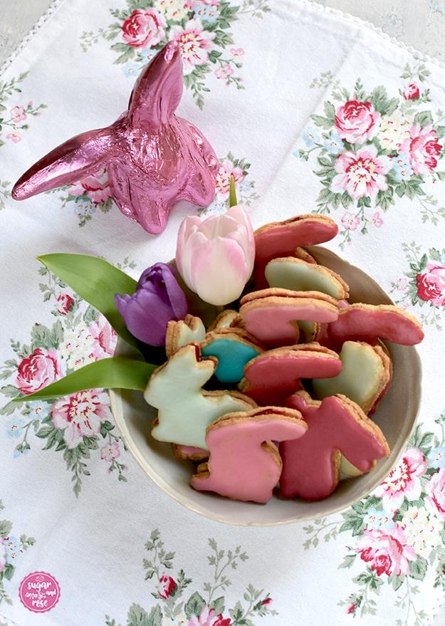 Osterhasen-Kekse in einer hellen Porzellanschale mit Tulpenblüte, dahinter ein pinkfarbener Schokoladenosterhase
