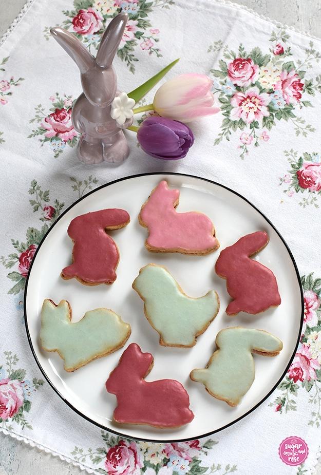 Osterhasen-Kekse in hell- und dunkelrosa und mintgrün auf einem weißen Porzeallanteller, dahinter ein fliederfarbener Porzeallanhase und zwei Tulpen in rosa und flieder