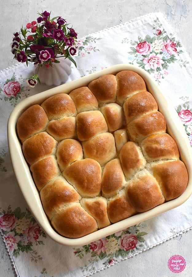 Marillenbuchteln frisch gebacken in einer Riess-Pfanne auf Serviette mit Rosenmuster, daneben eine kleine rosa Vase mit Bartnelken
