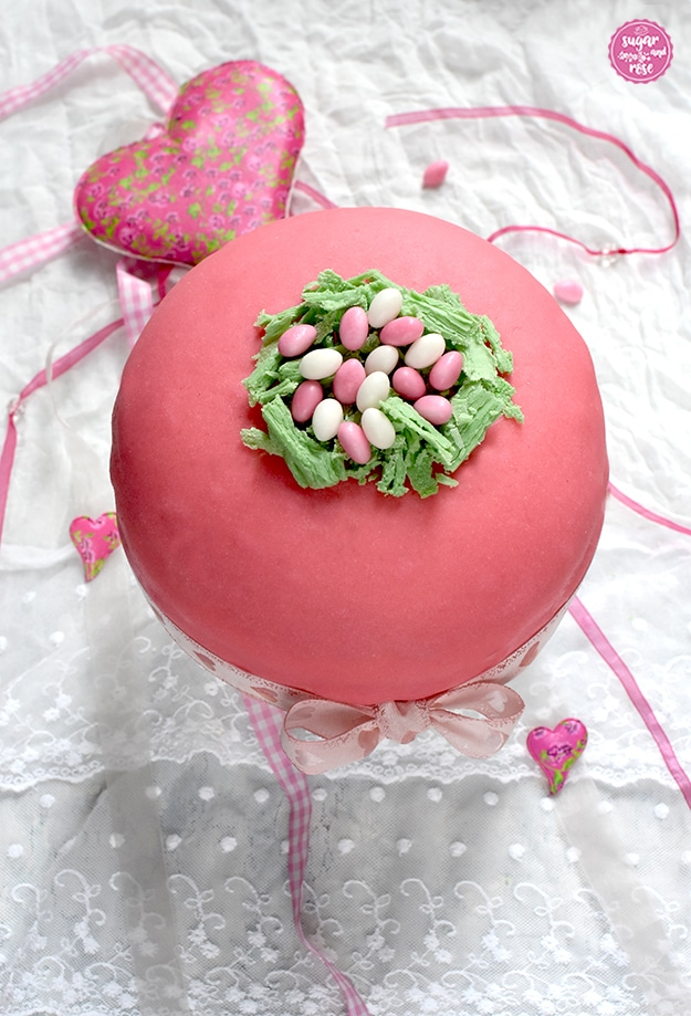 Rosa Ostertorte mit rosa und weißen Zuckereiern im Schokoosternest auf weißem Tortenständer von oben, dahinter ein rosa Herz und rosa Bänder