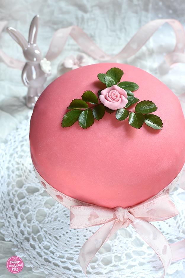 Ostertorte mit rosa Marzipanrose und grünen Rosenblättern dekoriert (Prinzessinnentorte), mit zartrosa Schleife mit Herzmotiven umwickelt, dahinter ein Porzellanosterhase