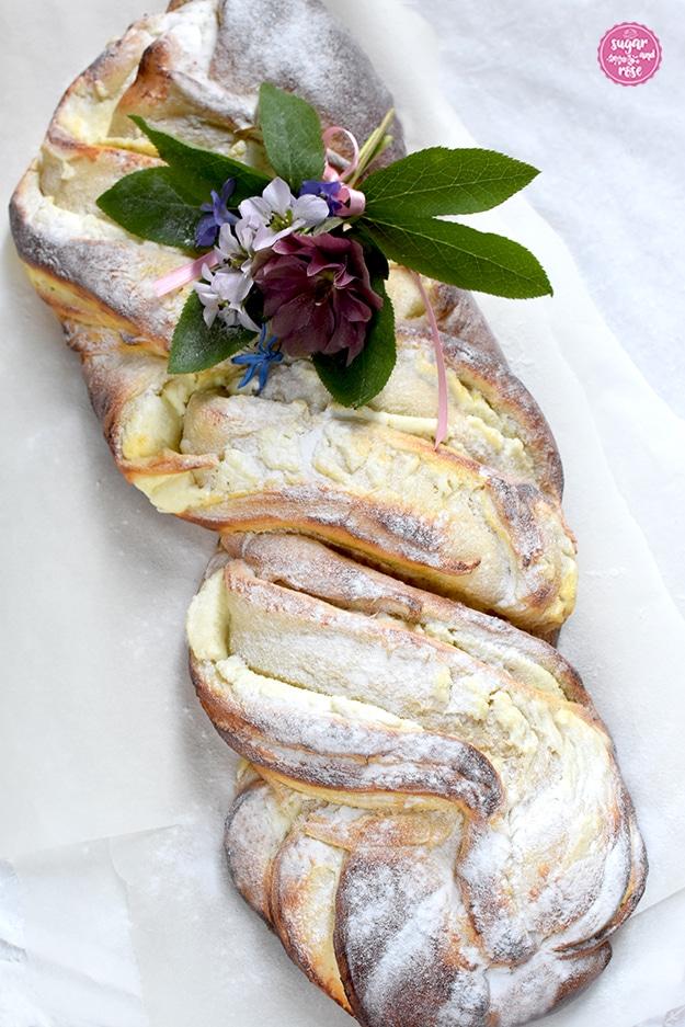 Topfen-Brioche auf Butterbrotpapier, dekoriert mit einem Frühlingsblumensträußchen