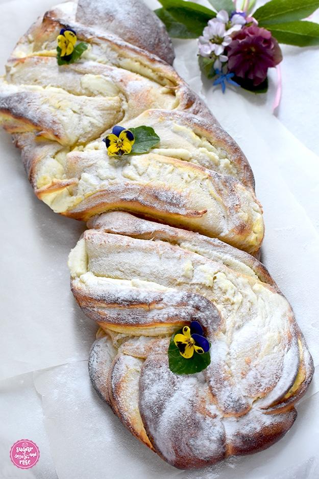 Topfen-Brioche auf Butterbrotpapier, mit Puderzucker und kleinen violett-gelben Violen dekoriert