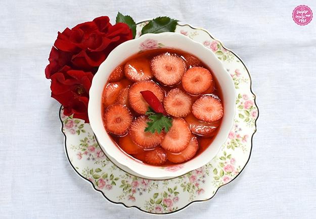 Erdbeerkompott in einer Dessertschüssel auf einem Blütendessertteller, dekoriert mit einer roten Rosenblüte.