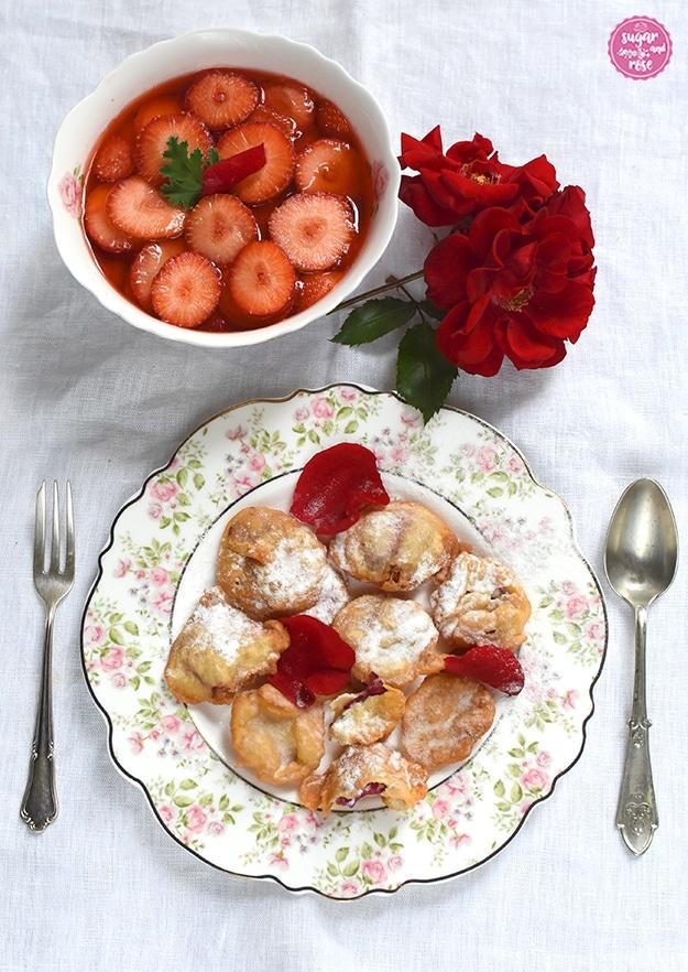 Gebackene rote Rosenblüten auf einem Dessertteller mit kleinen Röschen am Rand, daneben eine antike Dessertgabel und -löffel, dahinter eine Schale mit Erdbeerkompott und Blüten einer roten Rose.