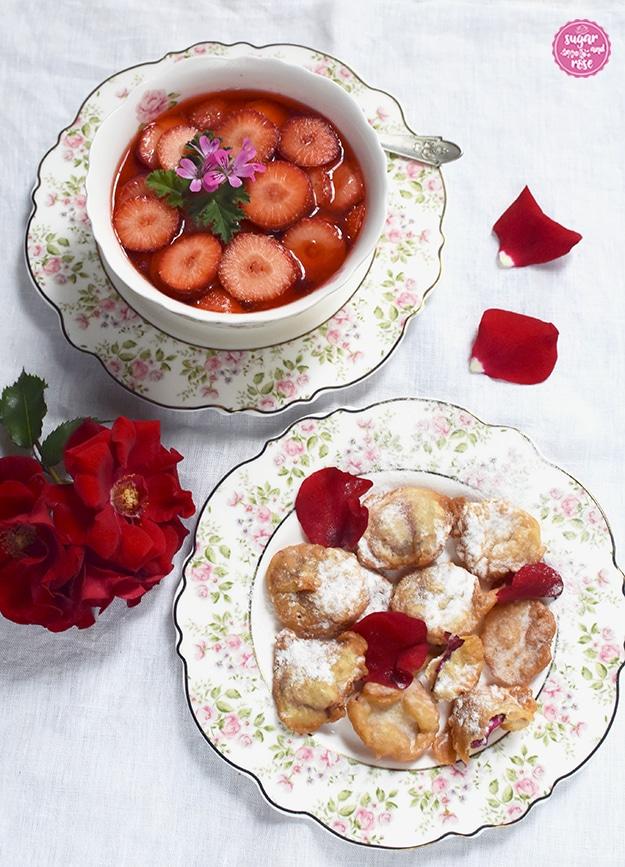 Gebackene rote Rosenblüten auf einem Dessertteller mit kleinen Röschen am Rand, dahinter eine Schale mit Erdbeerkompott und Blüten einer roten Rose und einige rote Rosenpetalen.