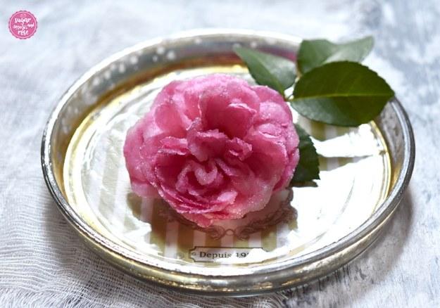 Eine kandierte ganze Rosenblüte mit grünem Blatt auf einem kleinen Bauernsilber-Tellerchen