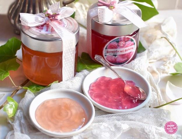 Zwei Gläser mit Rosengelee, davor zwei kleine Tellerchen mit Gelee, eines mit rosa Gelee, eines mit pfirsichfarbenem, dahinter ein Silberkännchen und Efeuranken