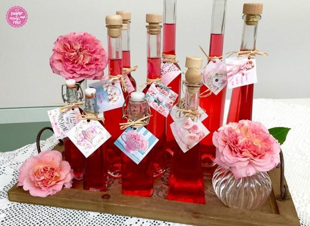 Roter Rosensirup in Flaschen abgefüllt und mit Rosenetiketten beschriftet auf einem Holztablett stehend, daneben eine bauchige kleine Glasvase mit Augusta-Luise-Rosenblütenköpfen