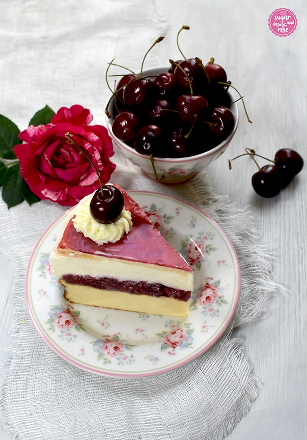Ein Stück Topfen-Kirschtorte auf einem Desserteller mit rosa Rosenblüten und kleinen Vergissmeinnicht. Die Schichten der Torte sind gut zu sehen: unten der gelbe Topfenkuchen, dann die rote Kirschschicht, darüber die weiße Topfencreme und der zartrosa Blätterteigboden, garniert mit Schlaoberstupfen und Kirsche. Dahinter eine kleine Keramikschale mit gleichem Dekor wie der Teller, gefüllt mit Kirschen. Daneben eine pinkfarbene Henri-Matisse-Rose.