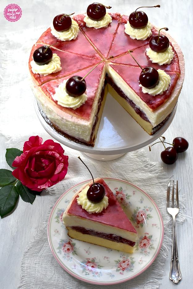 Topfen-Kirschtorte auf weißer Etagere, ein Stück ist herausgeschnitten. Vor der Torte ein Dessertteller mit kleinen Rosenmotiven, darauf ein Stück Torte, daneben Kirschen, eine Rosenblüte und eine silberne alte Dessertgabel.