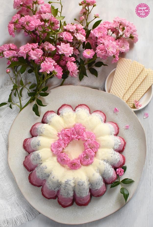 Eisgugelhupf von oben fotografiert, im Hintergrund mehrer Zweige mit rosa Röschen und ein kleiner weißer Teller mit Eiswaffeln.