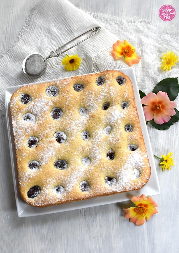 Obstkuchen mit Kirschen auf quadratischen weißen Teller, dahinter eine Zuckersieb und orange und gelbe offene Rosenblüten