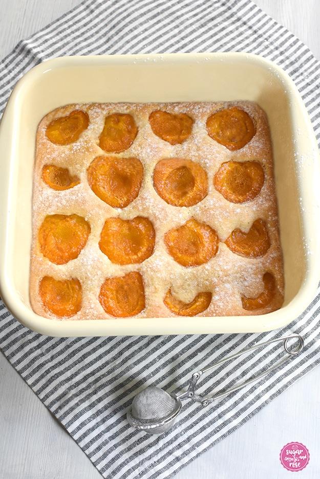 Obstkuchen mit Marillen in einer quadratischen Emailpfanne auf grau-weiß gestreifter Leinenserviette, davor ein Zuckerstreuer