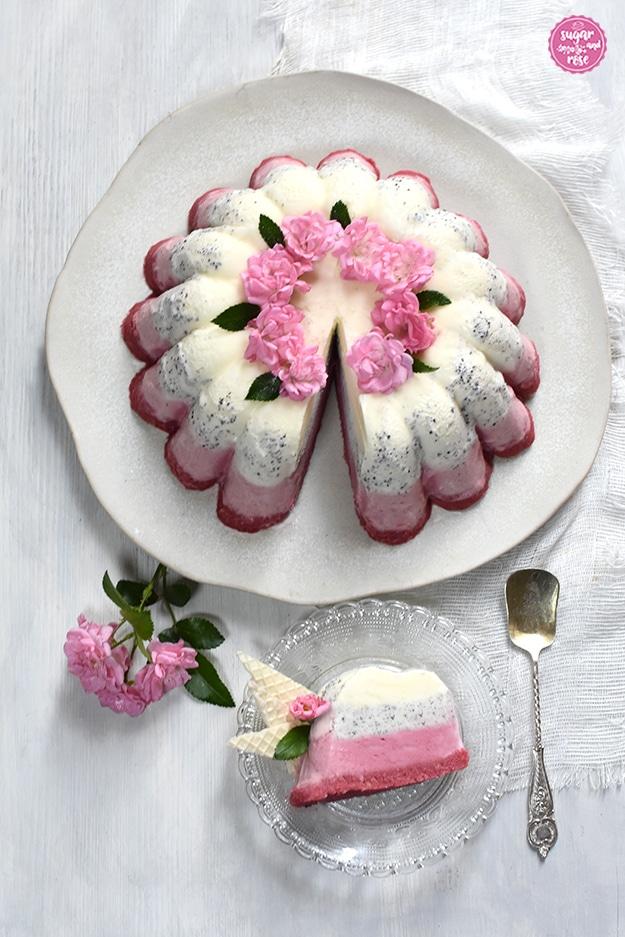 Eisgugelhupfanschnitt auf einem kleinen Teller, daneben ein silberner Eislöffel mit schönen Gravuren im Griff. Dahinter der Eisgugelhupf auf einem hellen Keramikteller.