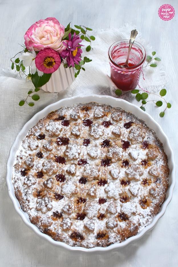 Linzer Torte in runder weißer Keramikform, mit Staubzucker bestäubt, dahinter eine kleine Vase mit einer weiß-rosa Rose, rosa Zinnien und grünen Blättern, daneben ein Glas Himbeergelee mit Silberlöffel