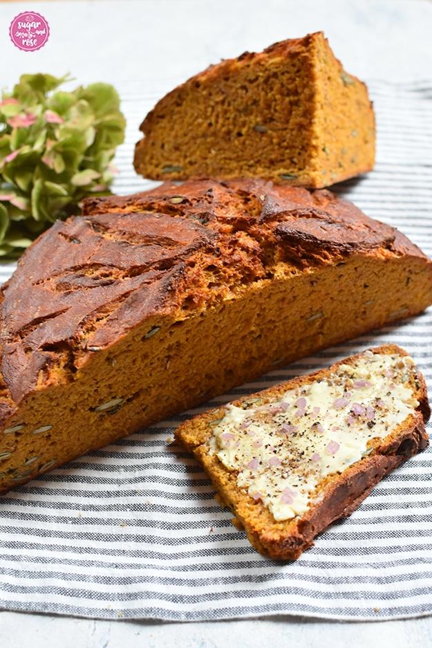 Halber Laib Kürbisbrot, dahinter ein Viertellaib und davor eine Scheibe Brot mit Butter und grobem rosafarbenen Salz