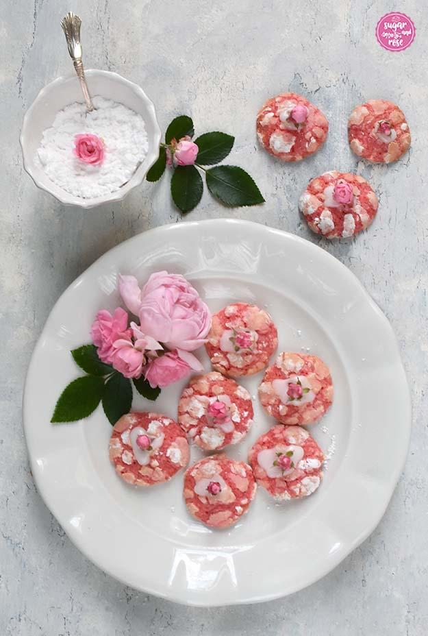 Rosen-Cookies auf altem weißen Keramikteller, dekoriert mit rosa Rosenblüten, dahinter ein kleine weiße Schale mit Staubzucker und einem Silberlöffel darin.