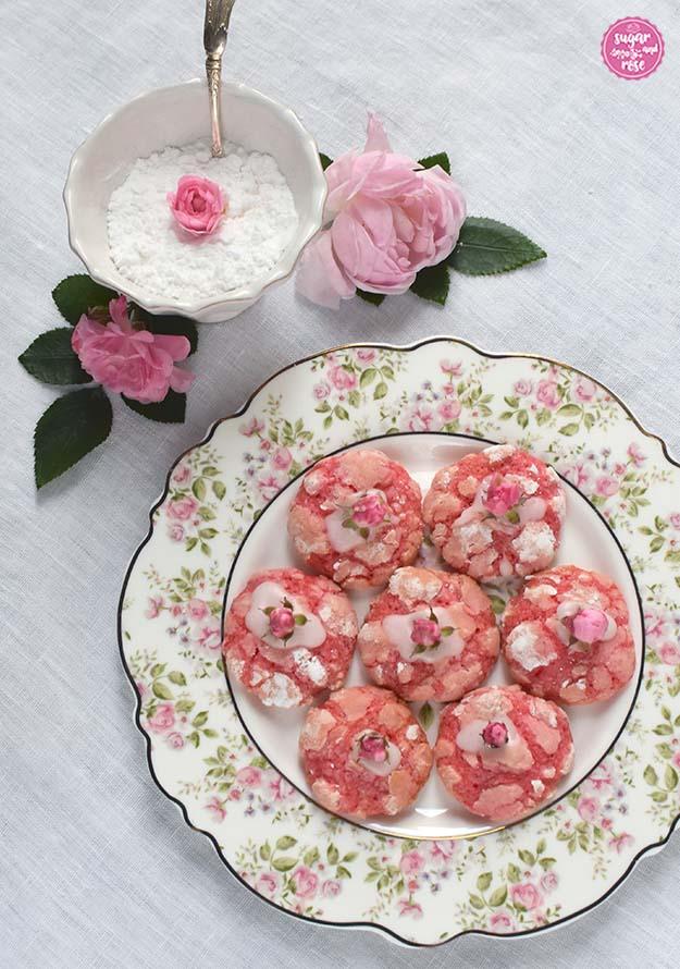 Ein weißer Porzellandesserteller mit Goldrand und dichtem Rosendekor am Tellerrand - gefüllt mit sieben im Kreis aufgelegten Rosen-Cookies. Als Deko dahinter wieder eine Zuckerschale und rosa Rosenblüten.