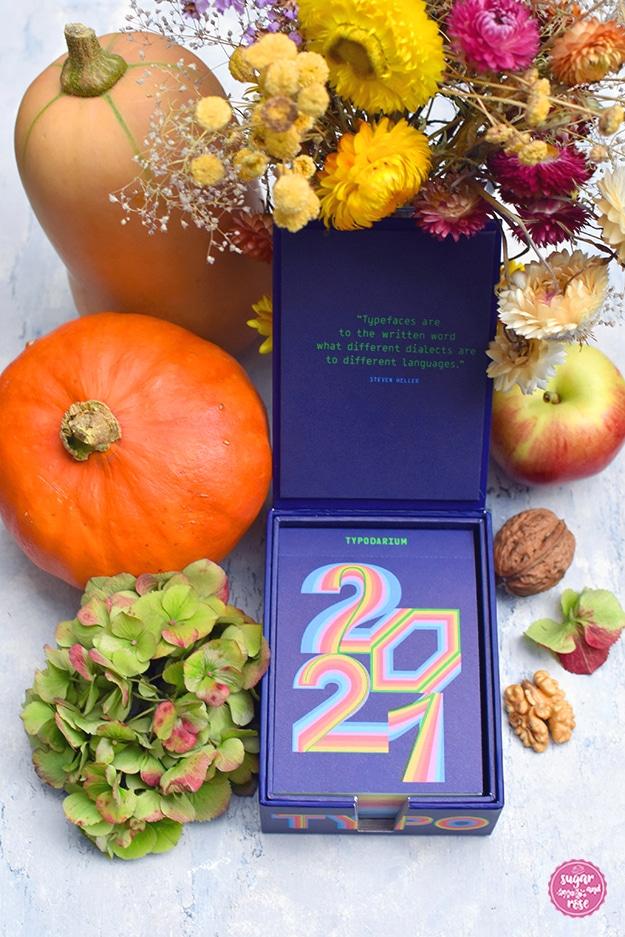 Typodarium-Tageskalender 2021 in blauer Kartonkasette, dekoriert mit zwei Kürbissen, Nüssen, Apfel und bunten Trockenblumen in herbstlichen Farben