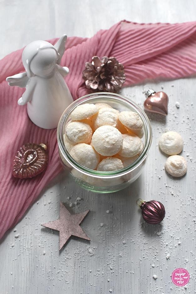 Kokosbusserl in einem Weckglas, dahinter ein rosa Schal, ein weißer Keramikengel und rosefarbener Weihnachtsschmuck