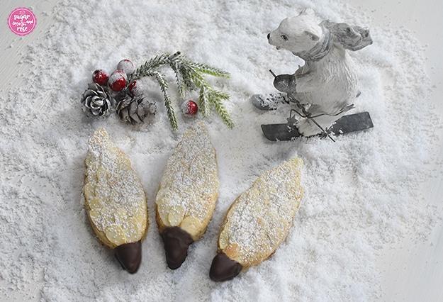 Drei Tannenzapfen-Kekse auf Kunstschnee, dahinter ein  Deko-Eisbär auf Schiern, ein grüner Zweig, weiß beschneite Bockerl und rote Kugerl