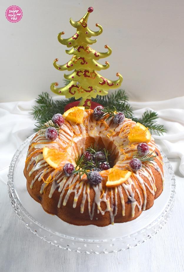 Orangen-Cranberry-Gugel auf einem gläsernen Kuchenteller mit Standfuß, dahinter ein grün-roter Weihnachtsbaum aus Keramik und Tannenzweige