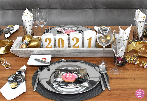 Tischmitte mit weißer länglicher Holzschale, darin vier weiße Kerzen, auf jeder eine goldene Ziffer (zusammen ergibt es die Jahreszahl 2021), daneben große goldene und kleine silberne Kugeln in der Schale, davor ein Platzteller in Silber mit Silberbesteck und weißer Stoffserviette, daneben ein Wein-, ein Sekt- und ein Wasserglas mit goldgepunkteter weißer Papierserviette