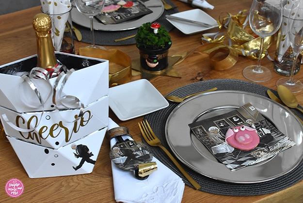 """Ein Gedeck mit Silber-Platzteller und Goldbesteck, einer Papierserviette mit Motiv """"Dinner for one"""" und Glückschweinchen-Kekse am Teller"""