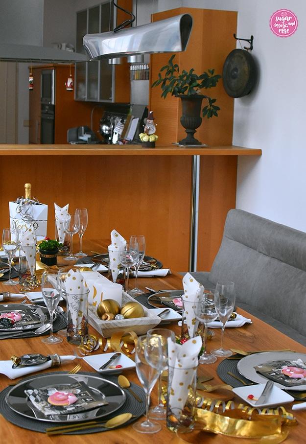 Mit sechs Gedecken in Silber und Gold dekorierter Esstisch aus Holz, in der Mitte eine weiße Holzschale mit goldenen Kugeln und weißen Kerzen, am Tisch Goldschleifen und Goldbesteck; im Hintergrund ein Blick in die Küche über eine Theke hinweg