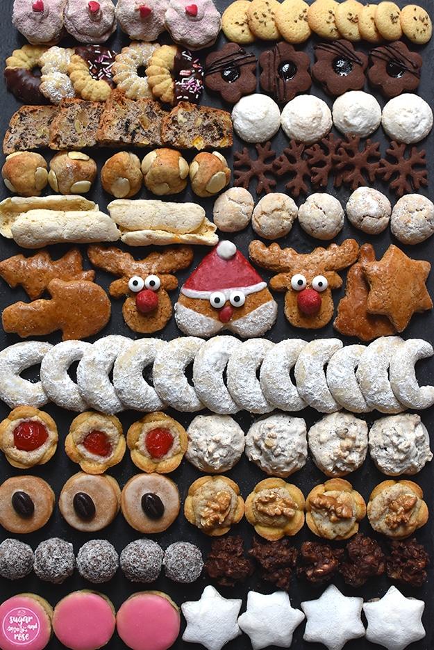 Schwarze Granitplatte im Hochformat, darauf in Reihen angeordnet die 20 im Text beschriebenen Kekssorten, in der Mitte ein rot glasierter Weihnachtsmann-Lebkuchen, daneben zwei Rentier-Lebkuchen mit roter Knollennase