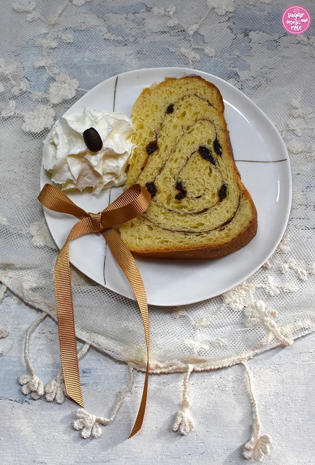 Ein Stück Kaisergugelhupf auf einem kleinen weißen Porzeallanteller mit goldfarbenen Linien, neben dem Kuchenstück etwas geschlagenes Obers mit einer Kaffeebohne getopt, daneben eine kleine zimtfarbene Seidenschleife