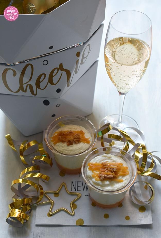 """Zwei Dessertgläschen mit Karamell-Mousse, Goldgirlanden, ein Sektkühler aus weißem Karton mit der Aufschrift """"Cheerio"""", daneben ein Glas Sekt"""