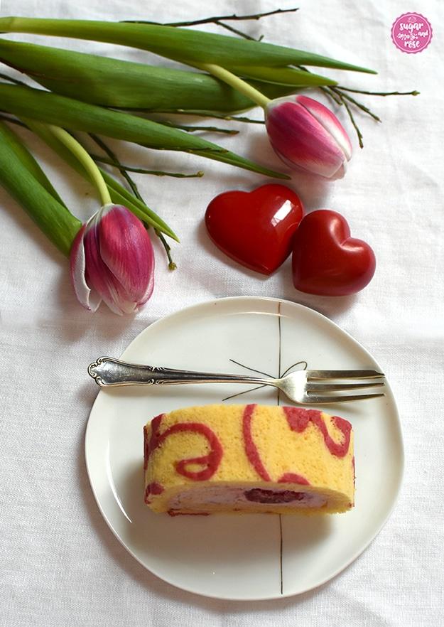 Ein Stück Biskutiroulde von oben fotografiert auf Porzellanteller mit Dessertgabel, dahinter wieder die roten Steinherzen eng aneinanderliegend und zwei rosa-weiße Tulpen