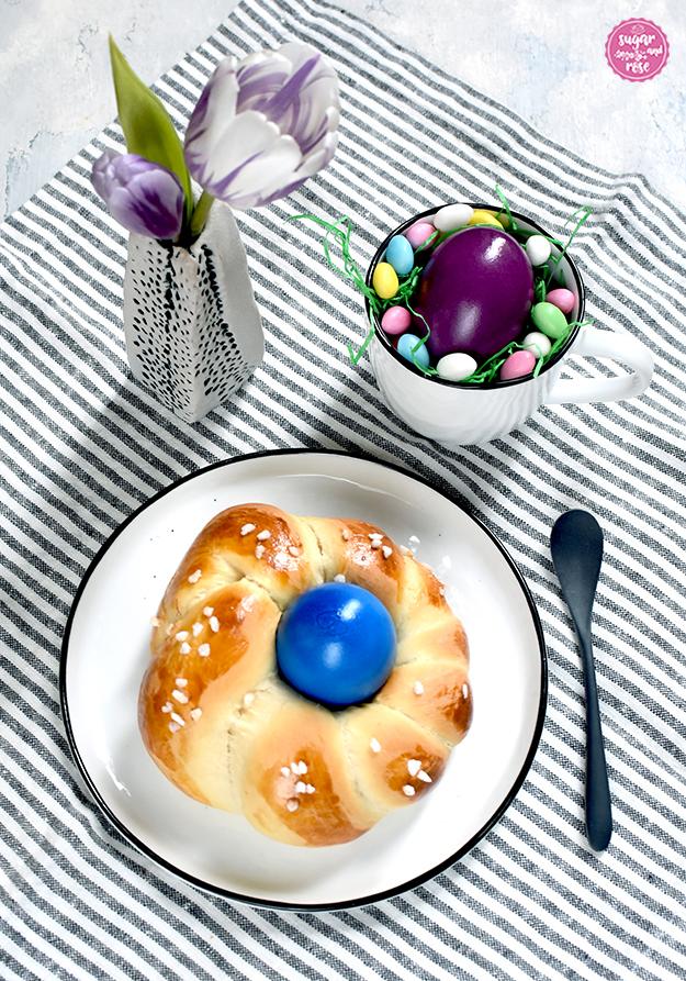 Im VordergRund ein weißer Teller mit dunkelblauem Rand, darauf ein Brioche-Osternest mit Hagelzucker und blauem Ei in der Mitte, daneben ein schwarzes Löffelchen, dahinter eine kleine graue Vase mit lila Tulpenblüten, daneben ein Häferl mit einem violetten Ei und rundum kleinen bunten Zuckereiern