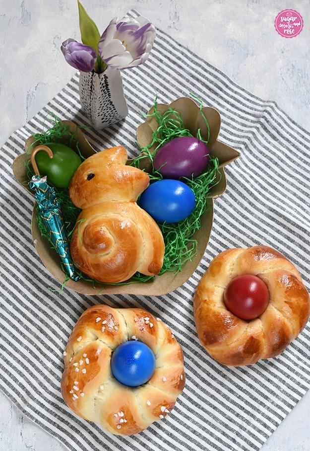 Auf grau-weiß gestreifter Leinenserviette ein Osternest aus Karton in Form einer Henne, gefüllt mit Brioche-Osterhasen, drei gefärbten Ostereiern, grünem Papierstroh und einem Schokoschirmchen, davor zwei Brioche-Osternester mit rotem und blauem Ei