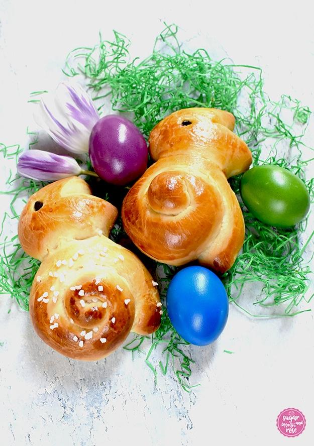 Zwei Brioche-Osterhasen auf grünem Papierstroh, je ein violettes, grünes und mittelblaues Ei und zwei violett-weiße Tulpenblüten