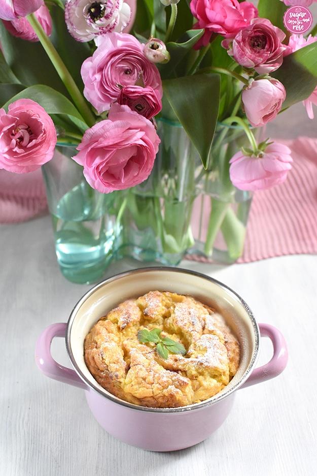 Hirse-Topfenauflauf im rosa Riess-Emaille-Reindl vor einer grünen Aalto-Vase mit rosa Ranunkeln, gezuckert und mit Zitronenmelisse garniert.