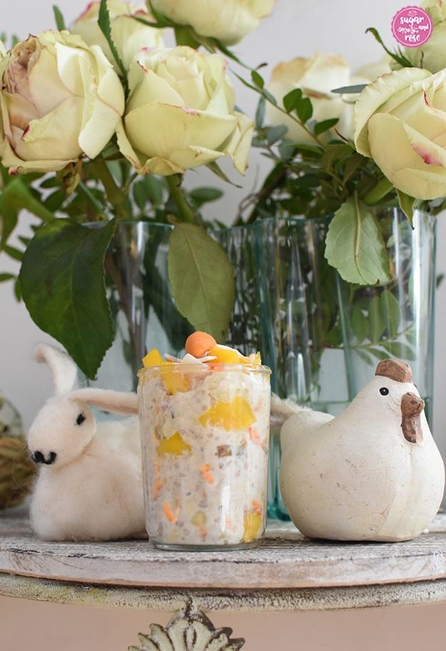Karotten-Overnight-Oats im Glas vor einem Strauß grün-weißer Rosen mit zarten rosa Rändern, daneben eine Henne aus weißem Gips mit braunem Kamm und ein Osterhase aus weißer Baumwolle.